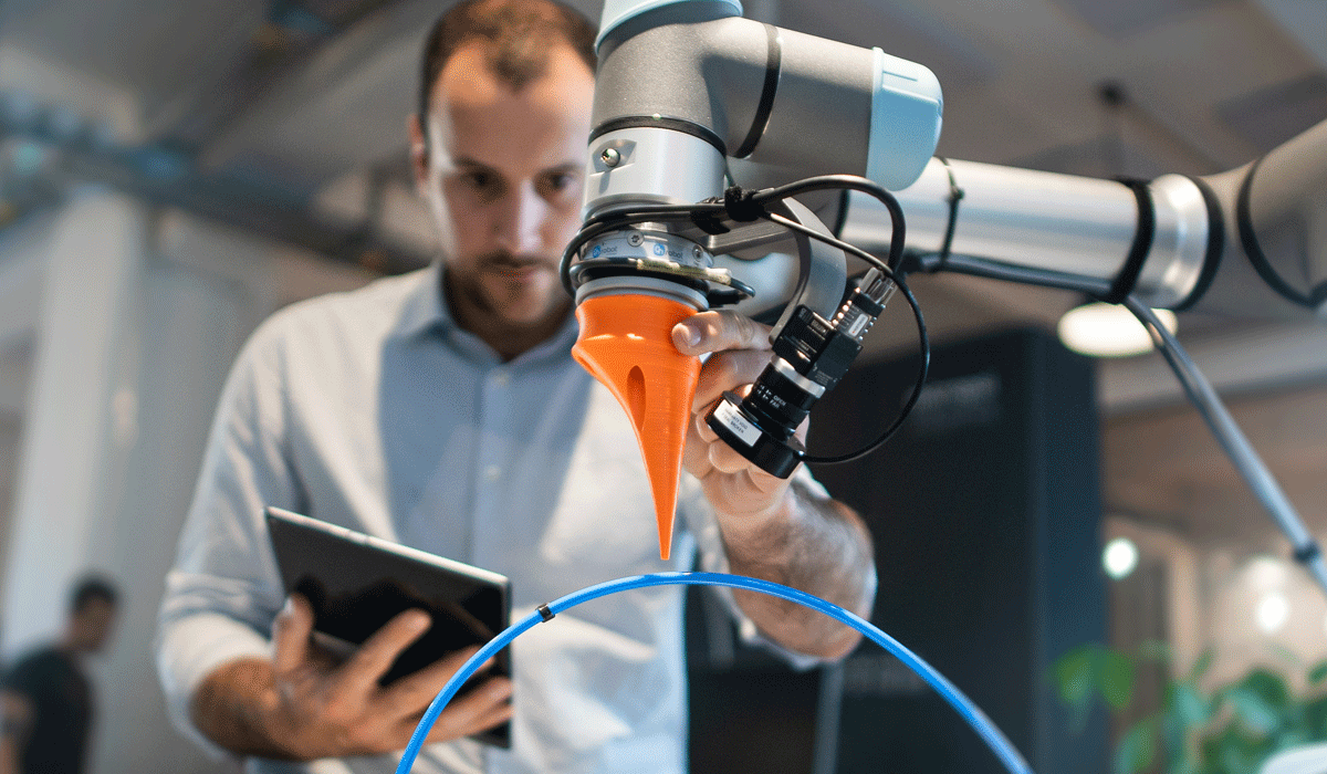 Man with tablet in hand in front of a robotic arm.